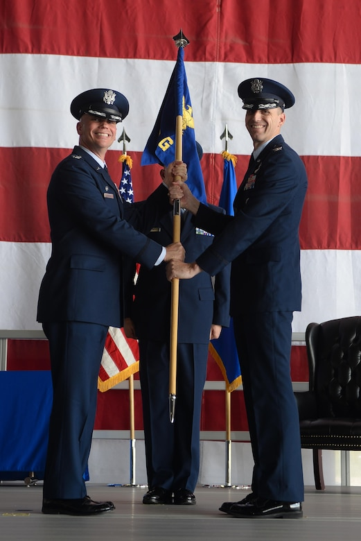 (Left) Col. Michael Manion, 55th Wing commander, hands off the guidon for the 55th Communications Group to (right) Col. Corey Ramsby during a change of command ceremony July 14, 2017 in the Bennie L. Davis Maintenance Facility on Offutt Air Force Base, Nebraska. The 55th CG's mission is to provide command, control, communications, computers and knowledge management services for the 55th Wing, U.S. Strategic Command, the 557th Weather Wing and more than 50 partner units. (U.S. Air Force photo by Zachary Hada)