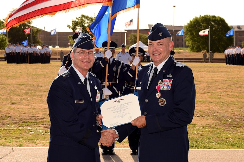 "U.S. Air Force Maj. Gen. Robert LaBrutta, 2nd Air Force Commander, presents the Legion of Merit certificate to Col. Michael Downs, 17th Training Wing Commander, at the parade field on Goodfellow Air Force Base, Texas, July 21, 2017. Downs was the 45th base commander and commands four groups, including three geographically separated units, with the mission, ""Develop Exceptional Intelligence, Surveillance and Reconnaissance and Fire Protection Professionals for America and Her Allies."" (U.S. Air Force photo by Airman 1st Class Randall Moose/Released)"