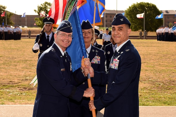 U.S. Air Force Maj. Gen. Robert LaBrutta, 2nd Air Force Commander, passes the guideon to Col. Ricky Mills, 17th Training Wing Commander, at the parade field on Goodfellow Air Force Base, Texas, July 21, 2017. Mills commanded the 17TRW from July 2017 until June 2019. (U.S. Air Force photo by Airman 1st Class Randall Moose/Released)