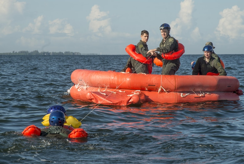 Service members from the Joint Communications Support Element and the 6th Air Mobility Wing swim to a raft and help each other onto a raft during a joint water survival exercise in Tampa Bay, Fla., July 18, 2017.  Once they all were on the raft, they began to simulate how to meet their basic needs of food, water, shelter and evasion. (U.S. Air Force photo by Senior Airman Mariette Adams)