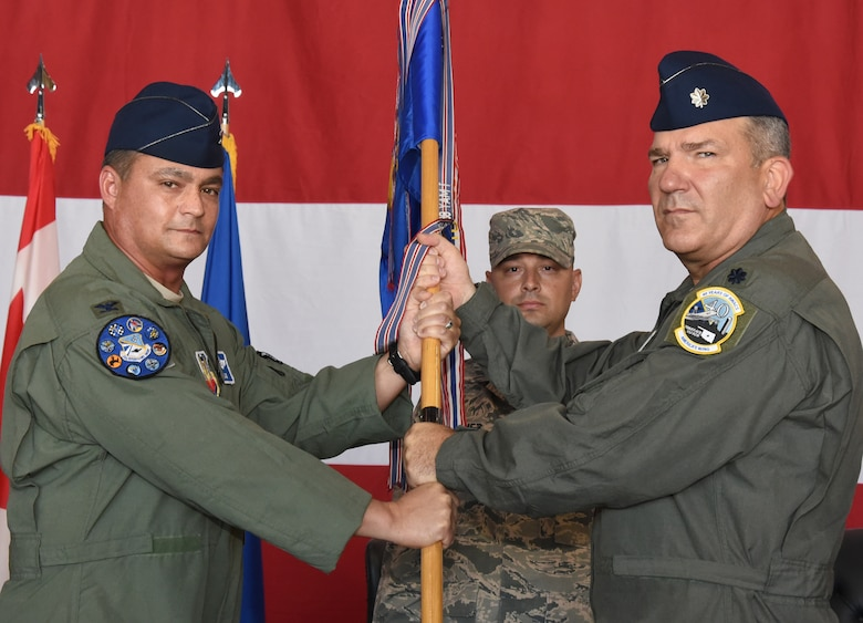 Lt. Col. Kirk Hansen, right, incoming commander of the 552nd Training Squadron accepts the unit guidon from Col. Richard Land III, 552nd Operations Group commander, during a change of command ceremony July 12, in Dock 2 of Hangar 230. Waiting to receive the guidon is Master Sgt. Antonio Quinonez, 552nd TRS first sergeant.