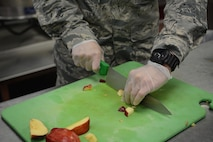 A services Airman cuts apples during meal preparation for Northern Lightning 2017 participants at Volk Field Air National Guard Base, Camp Douglas, Wis., May 9, 2017. The 40 services Airmen and Soldiers from across the nation prepared meals for approximately 6,500 exercise participants during the two-week exercise. (U.S. Air National Guard photo by Staff Sgt. Andrea F. Rhode)