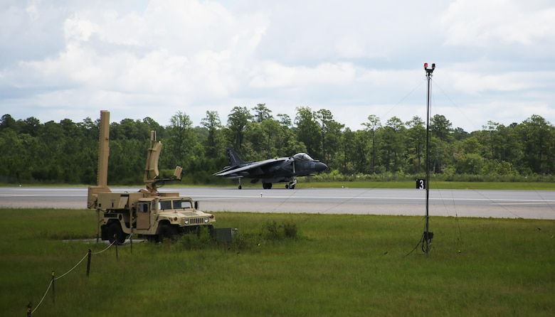 An AV-8B Harrier II lands on the runway next to the Air Traffic Navigation, Integration, and Coordination System at Marine Corps Air Station Cherry Point, N.C., July 19, 2017. The aircraft was tracked by the ATNAVICS before communication was transferred to Marines manning the air traffic control tower aboard the air station.  The Harrier is from Marine Attack Squadron 231, Marine Aircraft Group 14, 2nd Marine Aircraft Wing and MACS-2 is assigned to Marine Air Control Group 28, 2nd MAW. (U.S. Marine Corps Photo by: Pfc. Skyler Pumphret/ Released)