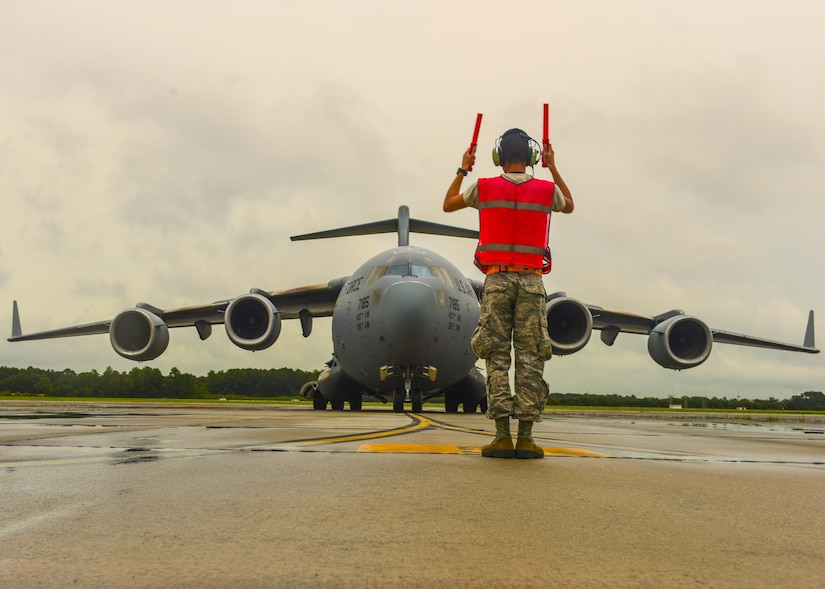 Airman 1st Class Steven Arroyo-Rivera, 437th Aircraft Maintenance Squadron crew chief, directs a C-17 Globemaster III on the flightline at Joint Base Charleston, S.C. July 17, 2017. The C-17's airlift capabilities are used to deploy U.S. armed forces anywhere in the world within hours. Additionally the C-17's help sustain troops in conflict, humanitarian, airlift, and airdrop efforts.