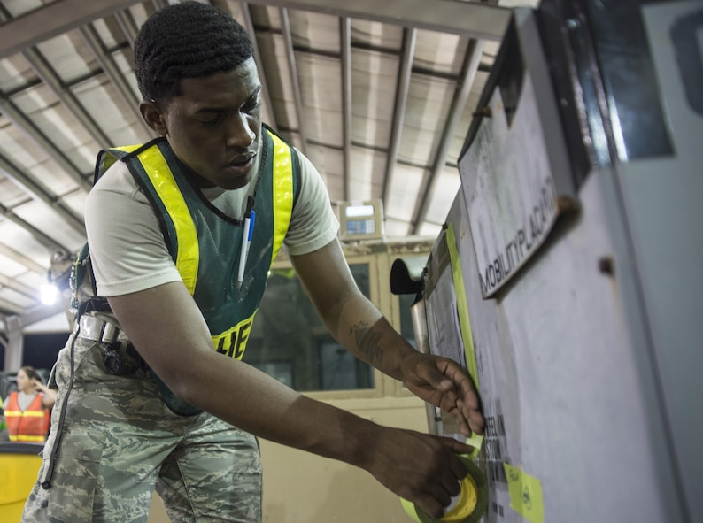 Airman 1st Class Marlon Cruz-Gonzalez, 4th Logistics Readiness Squadron travel management office, tapes cargo information to a heater cart's July 20, 2017, at Seymour Johnson Air Force Base, North Carolina. This process was a part of exercise Thunderdome 17-02, which is designed to evaluate the 4th Fighter Wing's ability to generate and deploy aircraft, Airmen and equipment. (U.S. Air Force photo by Tech. Sgt. David W. Carbajal)