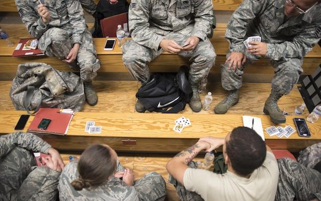 Airmen from the 4th Aircraft Maintenance Squadron play a game of spades while waiting at the pre-deployment function line processing center July 20, 2017, at Seymour Johnson Air Force Base, North Carolina. Airmen watched movies, played games and rested while waiting to be processed through the PDF line. (U.S. Air Force photo by Tech. Sgt. David W. Carbajal)