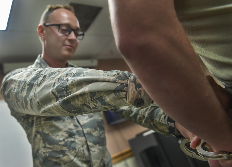 Airman 1st Class Aleksander Koziol, 437th Maintenance Squadron crew chief, handcuffs a simulated assailant during augmentee training at Joint Base Charleston, S.C., July 18, 2017. Augmentees attend a basic course for security forces procedures in case they are called to staff entry control points or conduct other security forces duties.