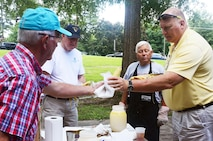 Tommy Wiggington, retired Chief Master Sgt. David Curtis, and retired Chief Master Sgt. Dallas Godfrey serve ears of corn to people attending the annual Corn and Sausage Roast held on Dobbins Air Reserve Base, Ga. July 19, 2017. The event's proceeds, along with assistance from the Dobbins Thrift Store, benefit the Dobbins Emergency Relief Fund. (U.S. Air Force photo/Don Peek)