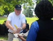 Retired Chief Master Sgt. David Curtis, serves ears of corn to an attendee at the annual Corn and Sausage Roast held on Dobbins Air Reserve Base, Ga. July 19, 2017. The event's proceeds, along with assistance from the Dobbins Thrift Store, benefit the Dobbins Emergency Relief Fund. (U.S. Air Force photo/Don Peek)
