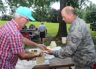 Tommy Wiggington serves up an ear of corn to Tech. Sgt. Blane Lopez from the 80th Aerial Port Squadron, at the annual Corn and Sausage Roast held on Dobbins Air Reserve Base, Ga. July 19, 2017. The event's proceeds, along with assistance from the Dobbins Thrift Store, benefit the Dobbins Emergency Relief Fund. (U.S. Air Force photo/Don Peek)