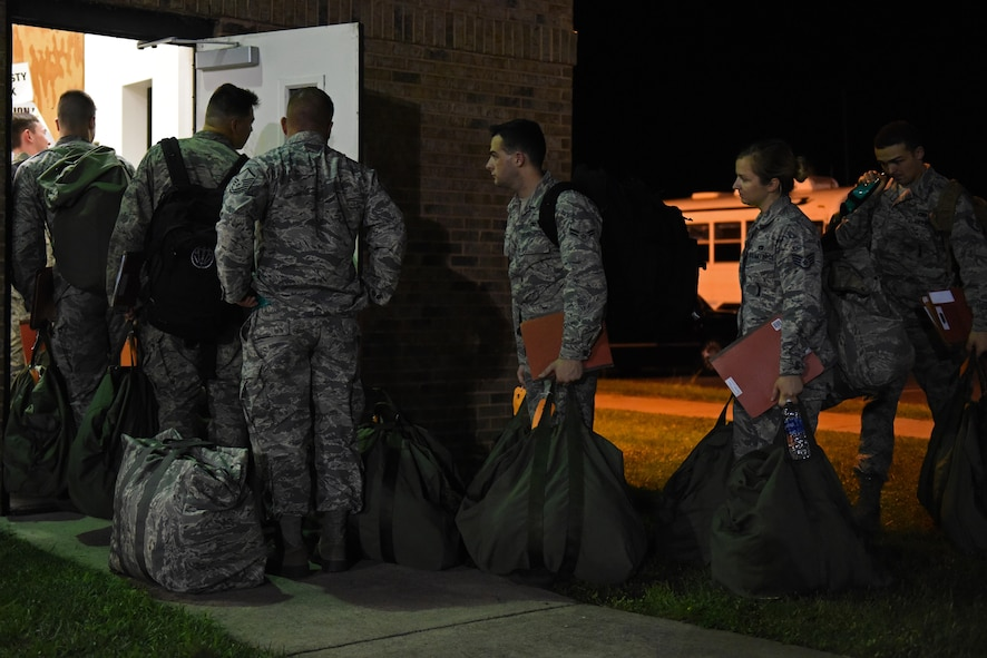 Team Seymour Airmen carry their deployment bags to the pre-deployment function processing center during Exercise Thunderdome 17-02, July 20, 2017, at Seymour Johnson Air Force Base, North Carolina. Seymour Johnson AFB members simulate deployments and other major events to test and improve readiness and capabilities. (U.S. Air Force photo by Senior Airman Ashley Maldonado)