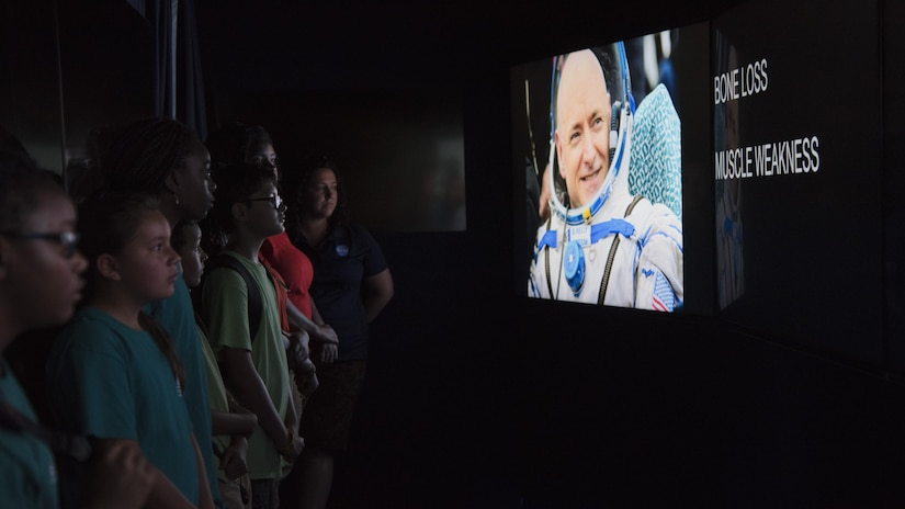 Participants watch a video in a mobile exhibit during a National Aeronautics and Space Administration's Science, Technology, Engineering, and Mathematics Day at Joint Base Andrews, Md., July 14, 2017. Attendees learned about the International Space Station's role in human exploration efforts that allow the space program to perform experiments and scientific research in microgravity. (U.S. Air Force photo by Airman 1st Class Valentina Lopez)