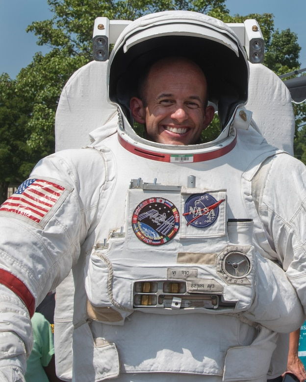 Col. E. John Teichert, 11th Wing and Joint Base Andrews commander, poses for a photograph in a spacesuit during a National Aeronautics and Space Administration's Science, Technology, Engineering, and Mathematics Day at Joint Base Andrews, Md., July 14, 2017. Participants learned about astronaut nutrition, spaceman suits and the International Space Station. (U.S. Air Force photo by Airman 1st Class Valentina Lopez)