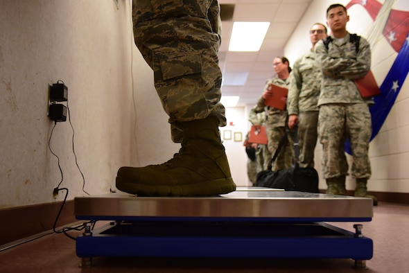 An Airman from Team Seymour stands on a weight scale while processing during exercise Thunderdome 17-02, July 20, 2017, at Seymour Johnson Air Force Base, North Carolina. During the exercise, deploying members were identified, medically cleared, equipped with any necessary gear and briefed on all information needed to conduct operations in the simulated area of responsibility. (U.S. Air Force photo by Airman 1st Class Kenneth Boyton)