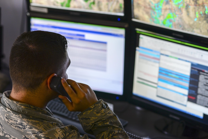 U.S. Air Force Airman 1st Class Cody Leahy, 25th Operational Weather Squadron forecaster, answers a phone call at Davis-Monthan Air Force Base, Ariz., July 19, 2017. Leahy was responding to weather condition inquiries from Travis AFB, Calif.  (U.S. Air Force photo by Airman 1st Class Michael X. Beyer)