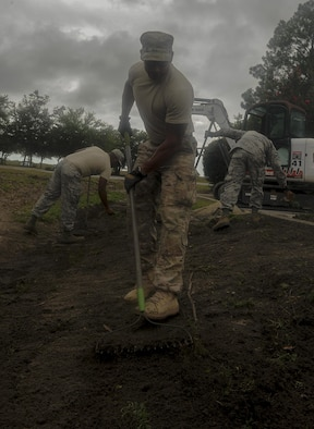 """Senior Airman Jason Mohamed, a pavements and construction equipment journeyman with the 1st Special Operations Civil Engineering Squadron, regrades a ditch on Hurlburt Field, Fla., July 18, 2017. The """"Dirt Boyz"""" from the 1st SOCES releveled a ditch outside the 1st Special Operations Medical Group, maintaining efficient storm drains and preventing flooding. (U.S. Air Force photo by Airman 1st Class Rachel Yates)"""