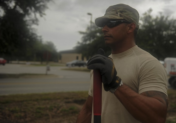 """Senior Airman Jason Mohamed, a pavements and construction equipment journeyman with the 1st Special Operations Civil Engineering Squadron, pauses during a construction project at Hurlburt Field, Fla., July 18, 2017. These Airmen, identified as """"Dirt Boyz,"""" are known for their work on roadways, pavements and the surrounding environment on Hurlburt. (U.S. Air Force photo by Airman 1st Class Rachel Yates)"""