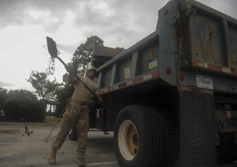 "Senior Airman Jason Mohamed, a pavements and construction equipment journeyman with the 1st Special Operations Civil Engineering Squadron, throws excess dirt into a dump truck at Hurlburt Field, Fla., July 18, 2017. The ""Dirt Boyz"" from the 1st SOCES releveled a ditch outside the 1st Special Operations Medical Group to maintain efficient storm drains and prevent flooding during heavy rain. (U.S. Air Force photo by Airman 1st Class Rachel Yates)"