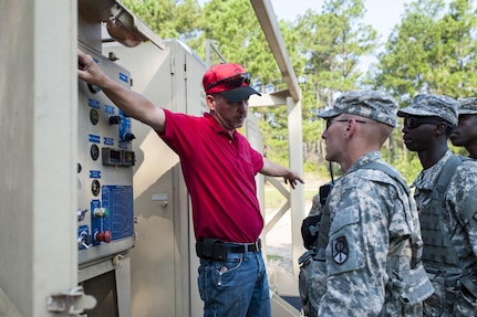 Brandon Howard, with the U.S. Army Forces Command's Petroleum Training Module, Fort Pickett, Va., discusses pump operations to U.S. Army Reserve Soldiers from the 728th Quartermaster Company, Fremont, Neb. during QLLEX 2017, July 21, at Fort Bragg, NC. QLLEX, short for Quartermaster Liquid Logistics Exercise, is the U.S. Army Reserve's premier readiness exercise for fuel and water distribution. This year's QLLEX is not only a full demonstration of the capability, combat-readiness, and lethality of America's Army Reserve to put fuel and water where it is needed most – in the vehicles and hands of the war-fighter and maneuver units – but it also further exercises the interoperability of the U.S. Army Reserve alongside active Army and British Army logisticians. (U.S. Army Reserve photo by Timothy L. Hale) (Released)