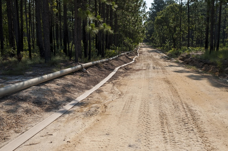Approximately 4-miles of 6-inch hose were installed along existing firebreaks and tactical trails during QLLEX 2017, July 21, at Fort Bragg, NC. QLLEX, short for Quartermaster Liquid Logistics Exercise, is the U.S. Army Reserve's premier readiness exercise for fuel and water distribution. This year's QLLEX is not only a full demonstration of the capability, combat-readiness, and lethality of America's Army Reserve to put fuel and water where it is needed most – in the vehicles and hands of the war-fighter and maneuver units – but it also further exercises the interoperability of the U.S. Army Reserve alongside active Army and British Army logisticians. (U.S. Army Reserve photo by Timothy L. Hale) (Released)