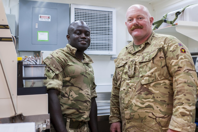 British Army logisticians, Staff Sgt. Samuel Korankye, left, and Staff Sgt. Barry Langley, both with the 152nd (North Irish) Regiment, Royal Logistics Corps, in Belfast, Northern Ireland, were attached the 53rd Quartermaster Company from Fort Hood, Texas, during QLLEX 2017, July 21, at Fort Bragg, NC. Langley, in the British Army Reserve, and Korankye, in the active British Army, were working with both U.S. Army Reserve and active Army logisticians during the QLLEX. QLLEX, short for Quartermaster Liquid Logistics Exercise, is the U.S. Army Reserve's premier readiness exercise for fuel and water distribution. This year's QLLEX is not only a full demonstration of the capability, combat-readiness, and lethality of America's Army Reserve to put fuel and water where it is needed most – in the vehicles and hands of the war-fighter and maneuver units – but it also further exercises the interoperability of the U.S. Army Reserve alongside active Army and British Army logisticians. (U.S. Army Reserve photo by Timothy L. Hale) (Released)