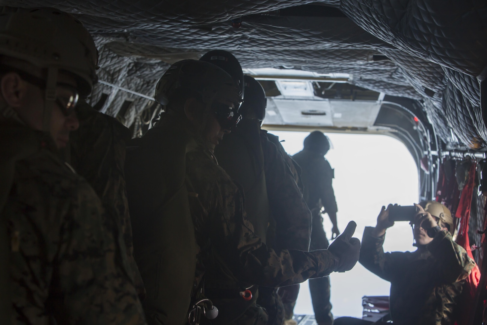 """SCHOFIELD BARRACKS – A Marine with 4th Force Reconnaissance Company gives the """"thumbs up"""" signal before conducting a high altitude airborne jump at Schofield Barracks, July 14, 2017. The Marines trained with U.S. Army Special Forces to maintain proficiency in completing static line and high altitude free fall airborne jumps. (U.S. Marine Corps photo by Lance Cpl. Isabelo Tabanguil)"""