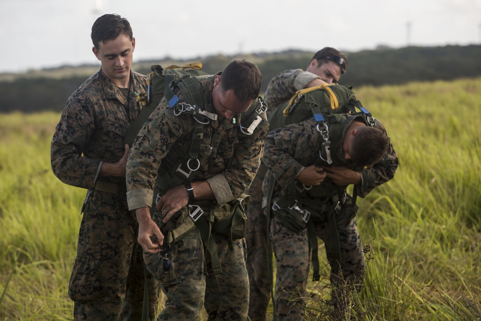 SCHOFIELD BARRACKS – Marines with 4th Force Reconnaissance Company prepare their parachutes before conducting a static line jump at Schofield Barracks, July 14, 2017. The Marines trained with U.S. Army Special Forces to maintain proficiency in completing static line and high altitude free fall airborne jumps. (U.S. Marine Corps photo by Lance Cpl. Isabelo Tabanguil)