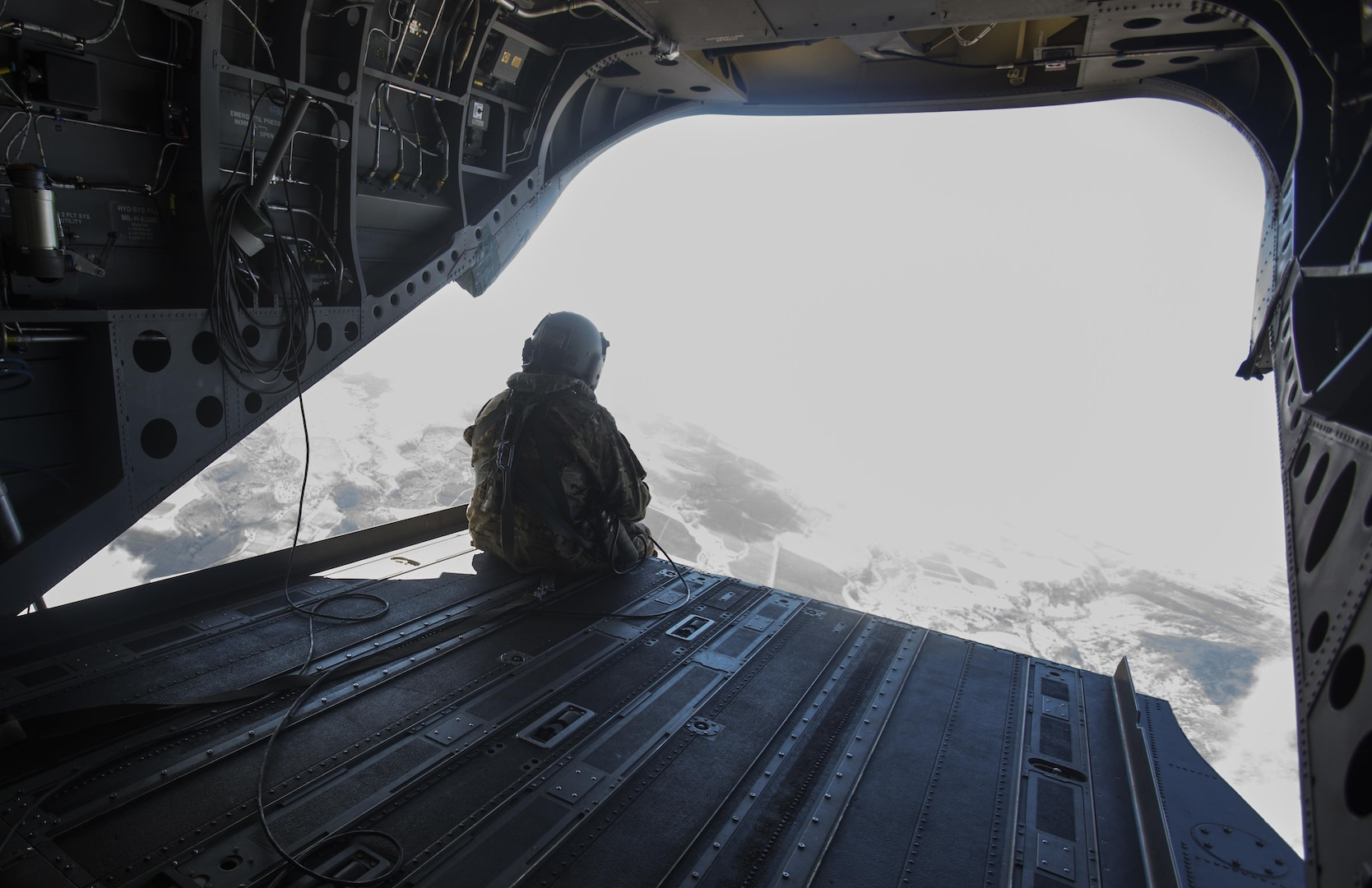 SCHOFIELD BARRACKS – A U.S. Army crew chief sits at the edge of a CH-47 Chinook helicopter ramp during a high altitude airborne jump at Schofield Barracks, July 14, 2017. Marines with 4th Force Reconnaissance Company trained with U.S. Army Special Forces to maintain proficiency in completing static line and high altitude free fall airborne jumps. (U.S. Marine Corps photo by Lance Cpl. Isabelo Tabanguil)