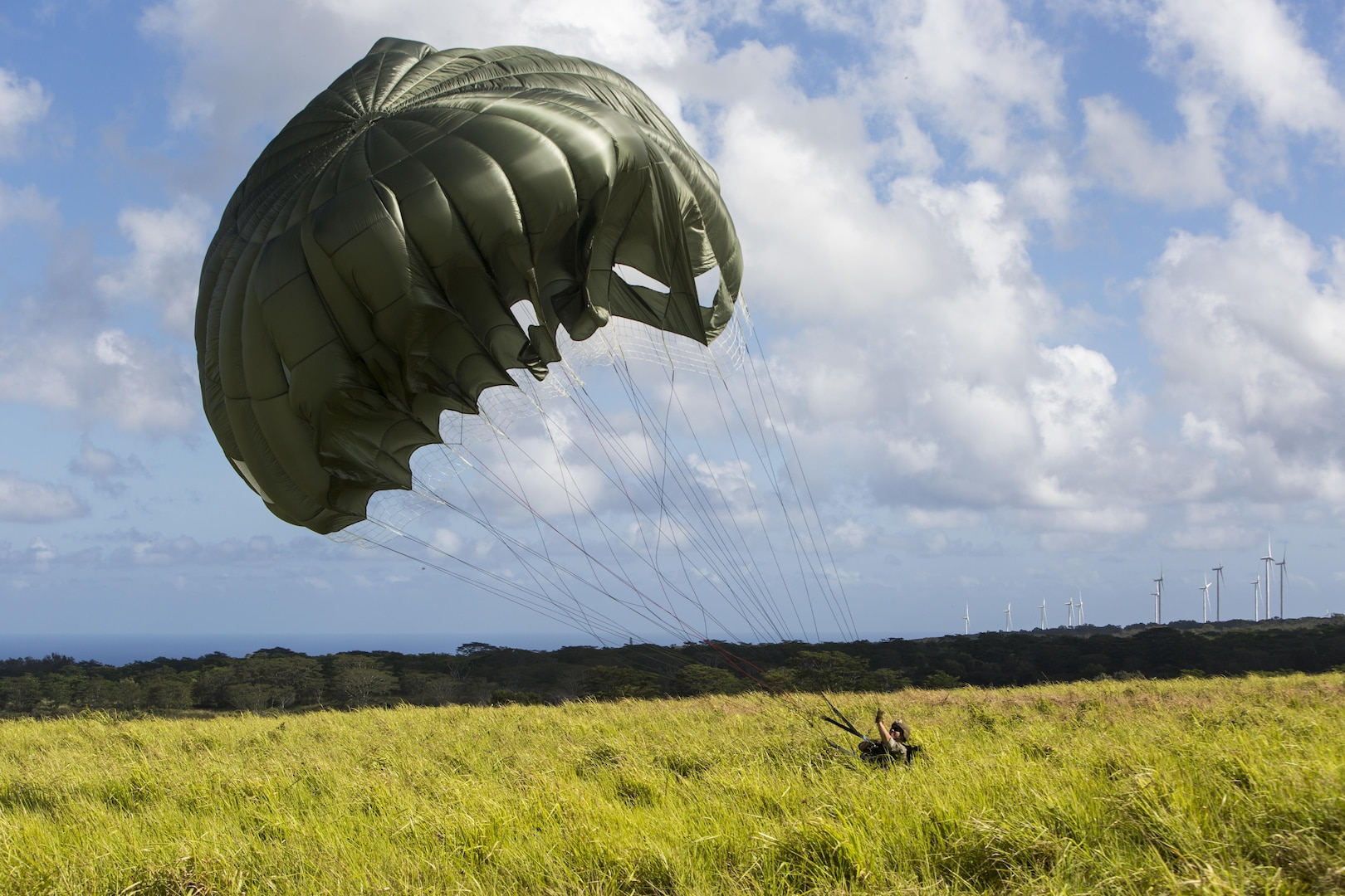 SCHOFIELD BARRACKS – A Marine with 4th Force Reconnaissance Company handles his parachute after successfully conducting a static line airborne jump at Schofield Barracks, July 14, 2017. The Marines trained with U.S. Army Special Forces to maintain proficiency in completing static line and high altitude free fall airborne jumps. (U.S. Marine Corps photo by Lance Cpl. Isabelo Tabanguil)