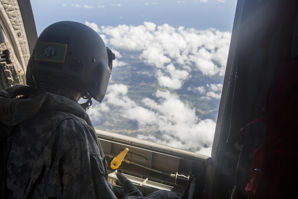 SCHOFIELD BARRACKS – A U.S. Army crew chief observes the outside of CH-47 Chinook helicopter during a high altitude airborne jump at Schofield Barracks, July 14, 2017. Marines with 4th Force Reconnaissance Company trained with U.S. Army Special Forces to maintain proficiency in completing static line and high altitude free fall airborne jumps. (U.S. Marine Corps photo by Lance Cpl. Isabelo Tabanguil)