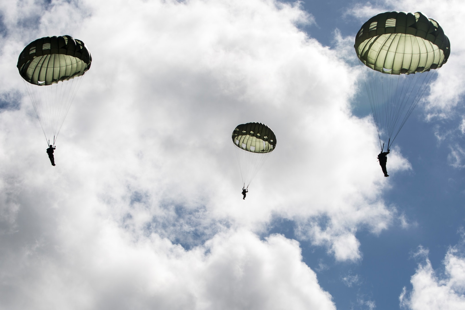 SCHOFIELD BARRACKS – Marines with 4th Force Reconnaissance Company descend after conducting a static line airborne jump from a CH-47 Chinook helicopter at Schofield Barracks, July 14, 2017. The Marines trained with U.S. Army Special Forces to maintain proficiency in completing static line and high altitude free fall airborne jumps. (U.S. Marine Corps photo by Lance Cpl. Isabelo Tabanguil)