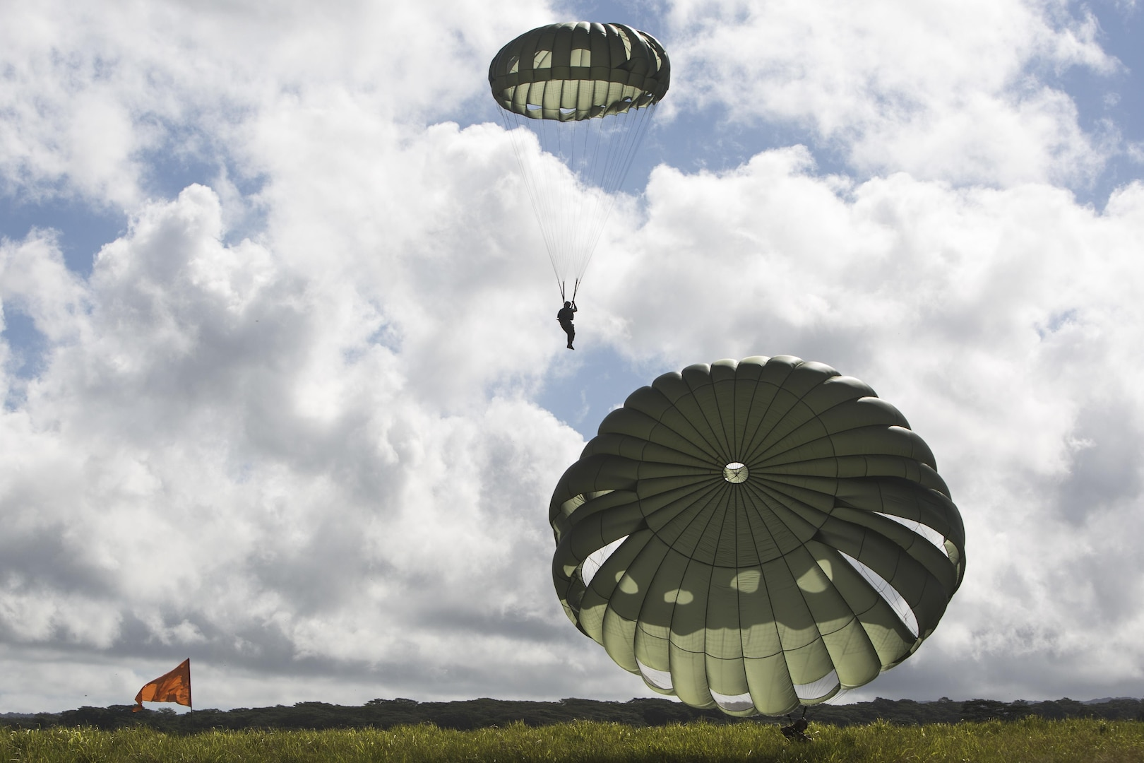 SCHOFIELD BARRACKS – Marines with 4th Force Reconnaissance Company land at a designated drop zone after conducting a static line airborne drop at Schofield Barracks, July 14, 2017. The Marines trained with U.S. Army Special Forces to maintain proficiency in completing static line and high altitude free fall airborne jumps. (U.S. Marine Corps photo by Lance Cpl. Isabelo Tabanguil)