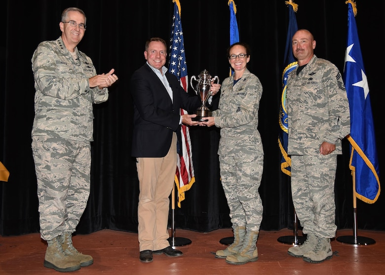 General John Hyten, commander of U.S. Strategic Command, and Tom Janssen, member of the strategic command consultation committee, present the Omaha Trophy to Col. Stacy Huser, 90th Missile Wing commander and incoming Command Chief Master Sgt. Kristian Farve during an all-call at the F. E. Warren Air Force Base, Wyo., theater July 21, 2017. The Omaha Trophy is awarded to the best missile wing in USSTRATCOM. (U.S. Air Force photo by Glenn S. Robertson)