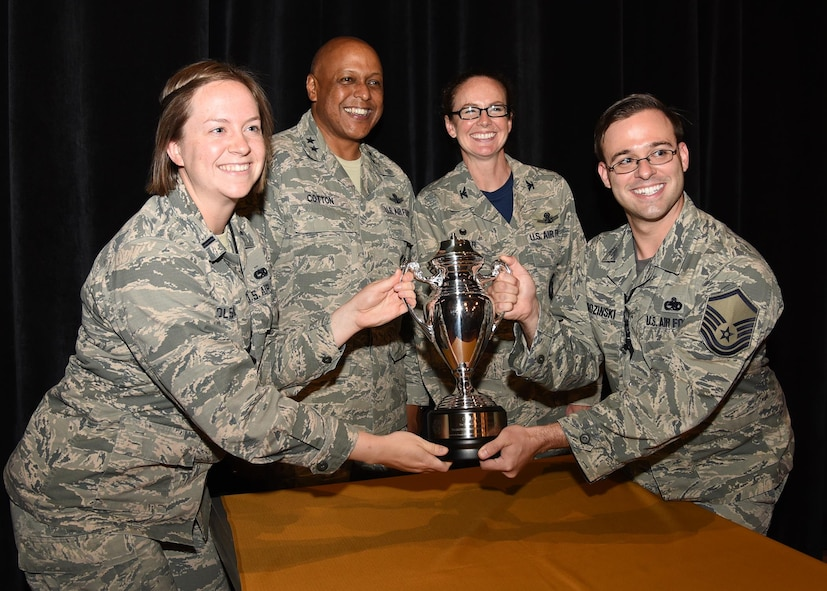 Members of the 90th Maintenance Group pose with the Omaha Trophy alongside Maj. Gen. Anthony Cotton, commander of 20th Air Force and Col. Stacy Huser, commander of the 90th Missile Wing after an all-call at the F. E. Warren Air Force Base, Wyo., theater July 21, 2017. The Omaha Trophy is awarded to the best missile wing in USSTRATCOM. (U.S. Air Force photo by Glenn S. Robertson)