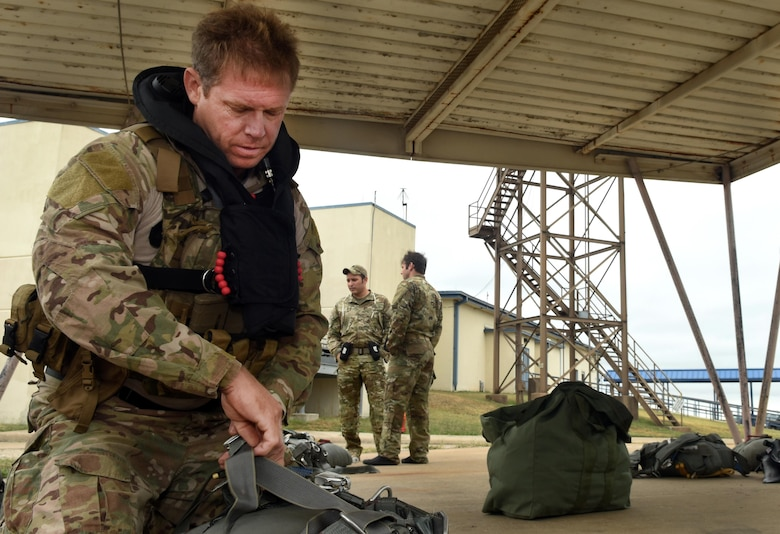 Senior Master Sgt. Andrew Hobbs, 181st Weather Flight superintendent, prepares to don his parachute equipment before a deliberate water drop into Lake Worth in Forth Worth, Texas, May 20, 2017. Hobbs is part of the Air Force Special Operations Weather Team, and as a member must undergo unique training to operate in hostile and denied territories to provide on-the-ground weather reporting. (Texas Air National Guard photo by Staff Sgt. Kristina Overton)