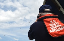 A member of the U.S. Coast Guard Auxiliary watches as members of the 181st Weather Flight parachute out of a C-130 Hercules during a deliberate water drop into Lake Worth in Forth Worth, Texas, May 20, 2017. The Coast Guard Auxiliary provided boat support to aid in parachute and jumper recovery, and provided medevac capabilities if necessary. (Texas Air National Guard photo by Staff Sgt. Kristina Overton)