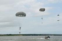 Members of the 181st Weather Flight parachute into Lake Worth after jumping out of a C-130 Hercules during a deliberate water drop in Forth Worth, Texas, May 20, 2017. The training mission was scheduled for members topractice airborne covert water parachute infiltration and included a joint effort between the Texas Air National Guard, Army, Coast Guard Auxiliary, and local fire department. (Texas Air National Guard photo by Staff Sgt. Kristina Overton)