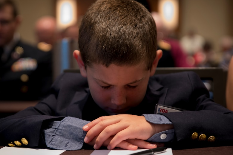 Elijah Daspit, son of Capt. Doug Daspit, U.S. Army Reserve chaplain for the 321st Sustainment Brigade, bows his head and prays during the opening invocation of this year's Reserve Officers Association National Convention held in Crystal City, Virginia, July 22, 2017. During the convention, Daspit was awarded Chaplain of the Year for his response to recent Baton Rouge floods, providing one-on-one pastoral counseling to 38 Soldiers and their affected families. (U.S. Army Reserve photo by Sgt. Audrey Hayes)