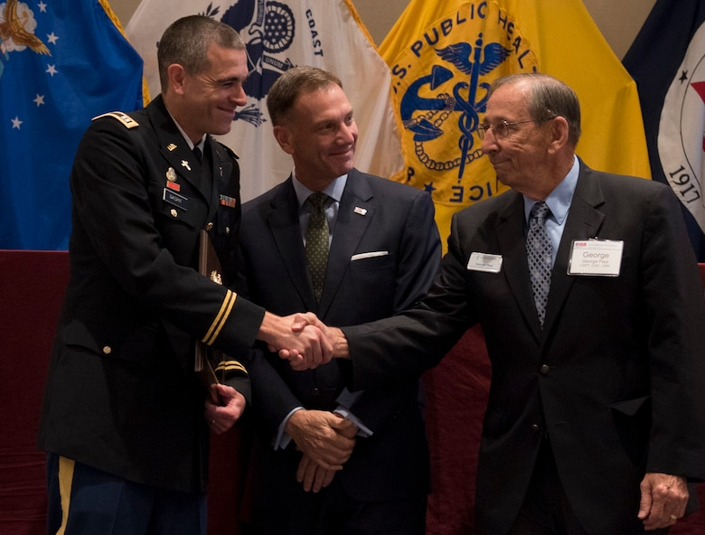 Capt. Doug Daspit, U.S. Army Reserve chaplain for the 321st Sustainment Brigade located in Baton Rouge, Louisiana, shakes hands with chaplain endorser, George Paul, after receiving the Chaplain of the Year award during the Reserve Officers Association National Convention in Crystal City, Virginia, July 22, 2017. Daspit was nominated for his response to recent Baton Rouge floods, providing one-on-one pastoral counseling to 38 Soldiers and their affected families. (U.S. Army Reserve photo by Sgt. Audrey Hayes)