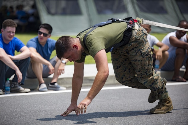 U.S. Marines with Marine Aviation Logistics Squadron (MALS) 12 pull a Humvee at Marine Corps Air Station Iwakuni, Japan, July 21, 2017. The USO hosted a field meet and cookout for MALS-12, which included several competitions such as grappling, pull-ups and a Humvee pull. (U.S. Marine Corps photo by Lance Cpl. Jacob A. Farbo)