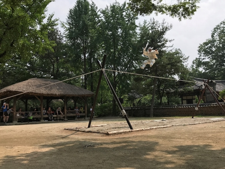 An acrobat performs a tightrope walking routine at the Korean Folk Village in Yongin, Republic of Korea, July 20, 2017. The Korean Folk Village hosts performances of traditional art forms from the Joseon Dynasty period to connect the past to the present. Nearly 100 United States Forces Korea members were invited by the Ministry of Patriots and Veterans Affairs to tour this location and other historic sites across the ROK as part of an initiative to give U.S. personnel a better understanding of Korean culture and patriotism. (U.S. Air Force photo by 1st Lt. Lauren Linscott/Released)