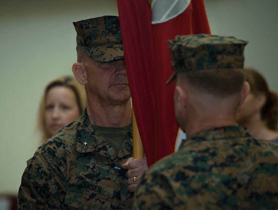 Brig. Gen. John M. Jansen passes the unit colors to Brig. Gen. Chris A. McPhillips during the 3rd Marine Expeditionary Brigade change of command ceremony at the theater on Camp Courtney, Okinawa, Japan, July 21, 2017. The ceremony symbolizes the exchange of responsibility to the new commanding general. McPhillips, the former 1st Marine Aircraft Wing assistant commander in Okinawa, Japan, assumed responsibility as the new commanding general of 3rd MEB. (U.S. Marine Corps photo by Lance Cpl. Andrew Neumann)