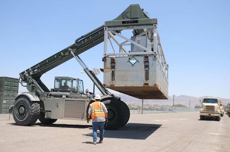 A portion of a Modular Causeway System (MCS) is moved into position so it can be loaded onto a 250th TC M915 truck for transport to the Port of San Diego as a part of Exercise Big LOTS West 17.