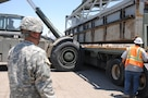 Sgt. Michael Tovar of the 250th Transportation Company out of El Monte, Calif., observes as section a Modular Causeway System (MCS) are loaded onto his M915 truck at the Marine Corps Logistics Base in Yermo, Calif., during Big LOTS West 17.