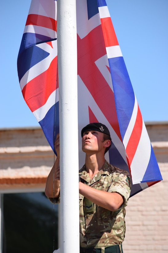 Lance Cpl. Brian Sutherland, 1st Battalion, The Rifles, 160 Brigade, raises the flag of Great Britain during the Exercise Steppe Eagle 17 opening ceremony July 22, 2017, at Illisky Training Center, Kazakhstan. (U.S. Army photo by Capt. Desiree Dillehay, 149th Military Engagement Team)