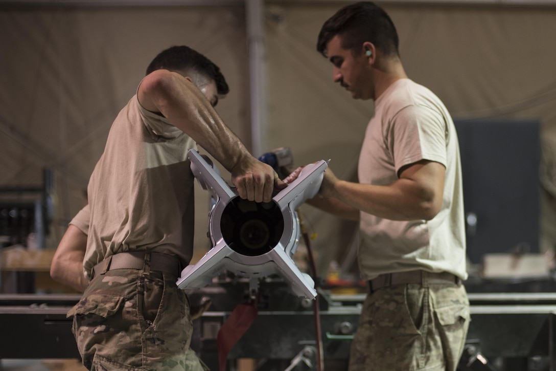 Staff Sgt. Noah Dankocsik, left, and Senior Airman Stefan Fleury, 332nd Expeditionary Maintenance Squadron maintenance crewmembers, install a tail kit to a GBU-12 laser-guided bomb July 7, 2017, in Southwest Asia. The 332nd EMXS must build a variety of bombs to combat the wide range of threats throughout the area of operation. (U.S. Air Force photo/Senior Airman Damon Kasberg)