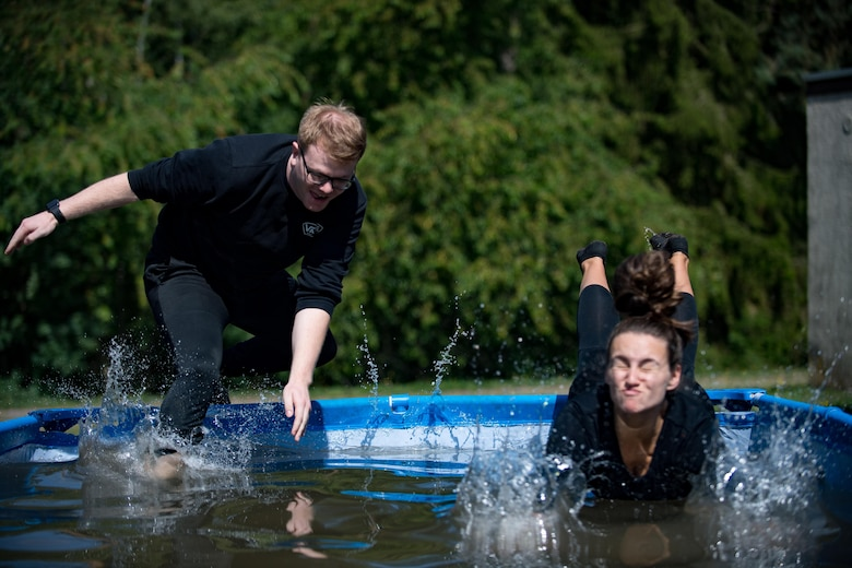 U.S. Air Force Senior Airman Michael Krawczyk and U.S. Air Force Staff Sgt. Jordan Hebner, both 86th Dental Squadron dental assistants, leap into a pool during the annual Mudless Mudder on Ramstein Air Base, Germany, July 21, 2017. If teams could not clear an obstacle, they were required to perform ten burpees to continue the race. (U.S. Air Force photo by Senior Airman Devin Boyer)