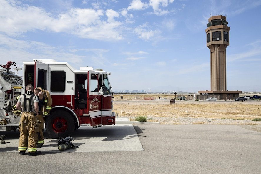 Firefighters assigned to the 99th Civil Engineer Squadron prepare their gear outside the air traffic control tower at Nellis Air Force Base, Nev., July 18, 2017. One of the team's training exercises is to climb the air traffic control tower's 10 stories to practice their readiness and emergency response capabilities. (U.S. Air Force photo by Airman 1st Class Andrew D. Sarver/Released)