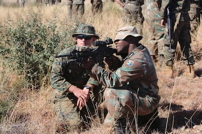 U.S. Marine instructs a member of the South African Navy's Maritime Reaction Squadron (MRS) on proper weapon handling procedures of the U.S. M27 Infantry Automatic Rifle during a familiarization fire range as part of Shared Accord 17 (SA17) at South African Army Combat Training Center, Lohatla, South Africa, July 19, 2017. During SA17 members of the MRS and U.S. Marines will form integrated units, building interoperability as they learn each others techniques, tactics, and procedures. SA17 is a Joint bi-lateral Field Training Exercise with our South African partners focused on Peace Keeping Operations designed to exercise participants' capability and capacity to conduct African Union / United Nations mandated Peace Keeping Operations. (U.S. Marine Corps photo by 2nd Lt. Brett Lazaroff/Released)