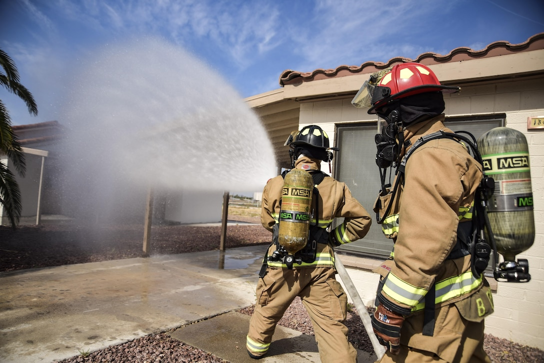 Airman 1st Class Brian Velten, 99th Civil Engineer Squadron firefighter, and Staff Sgt. Blaine Erway, 99th CES firefighter crew chief, use a firehose on a simulated house fire during Red Flag 17-3 at Nellis Air Force Base, Nev., July 18, 2017. Firefighters train for various situations to maintain their emergency response readiness. (U.S. Air Force photo by Airman 1st Class Andrew D. Sarver/Released)
